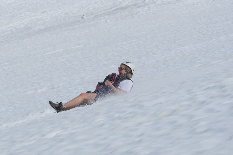 Women slides down Whistler Mountain glacier on a Glissade Tour