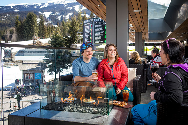 A couple enjoy apres in Whistler on a sunny bar patio.
