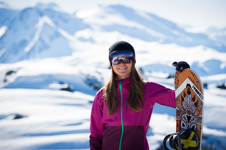 A snowboarder poses in the sunshine with the mountains in the background.