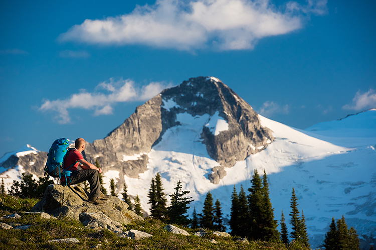 Man sitting on rock staring at mountain in Whistler