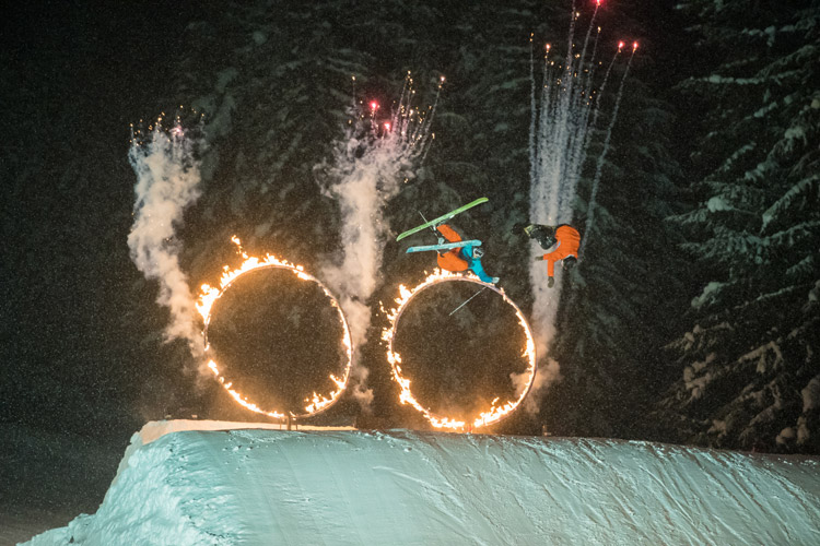 Skiers jumping through flaming hoops in the Fire & Ice Show