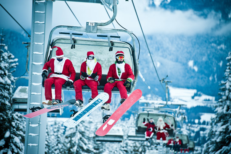 Skiers dressed as Santa on a chairlift in Whistler