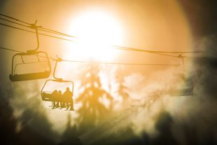 Silhouetted skiers on Whistler mountain