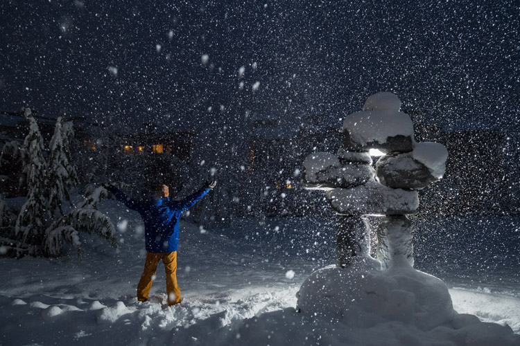 A man in snow gear, stood next to a snow-laden Inuksuk raises his arms to the evening sky as the snow falls in Whistler.