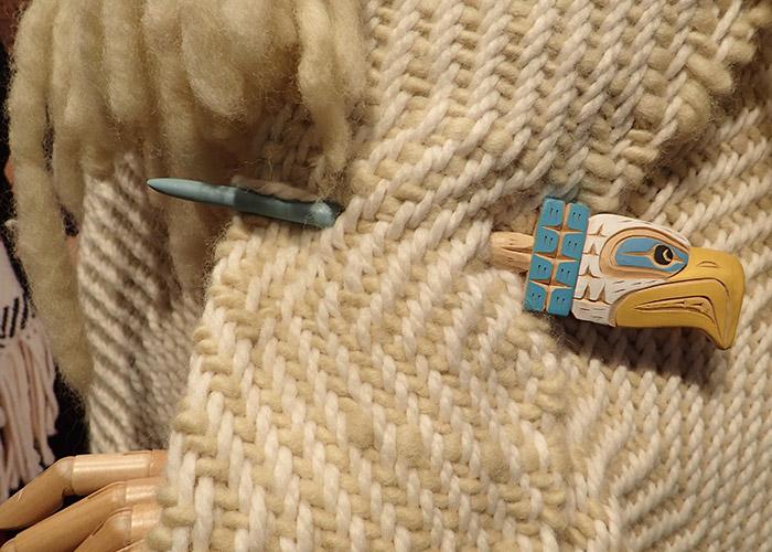 A beautiful handmade pin on a woven shawl.