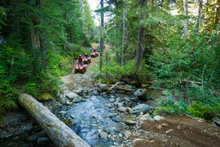 ATVs splash through a creek in Whistler.