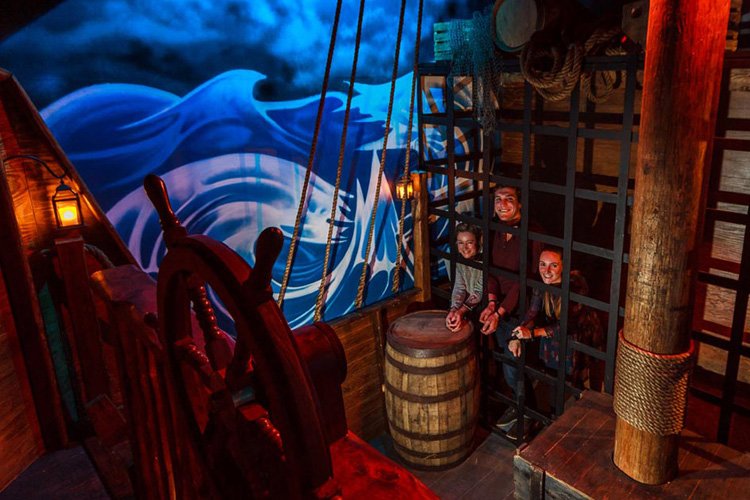 People locked in a cage in a pirate themed room.