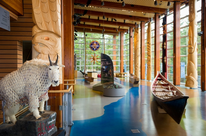Large room with floor to ceiling windows and native artifacts.