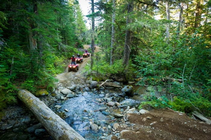 An ATV tour crossing a creek.