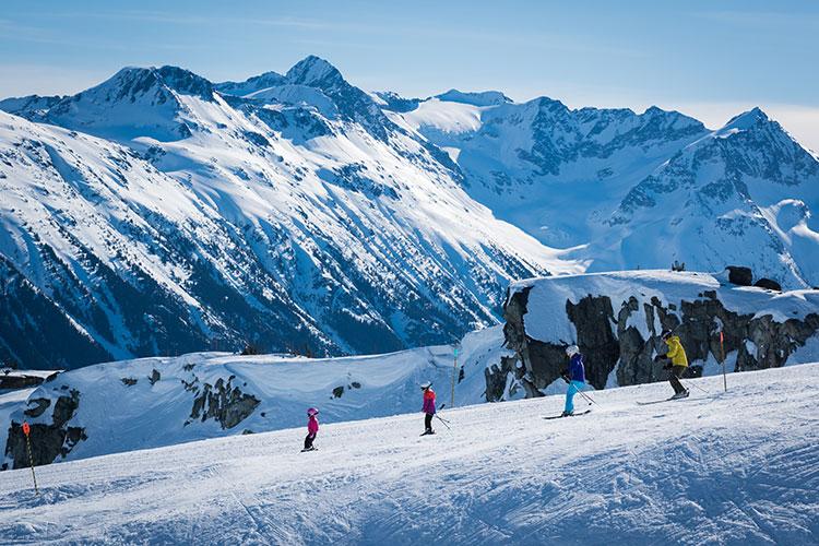 family skiing on a mountain top ridge