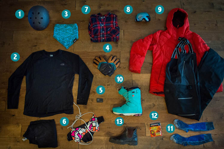 Goods laid out for what to pack for skiing and snowboarding from above.