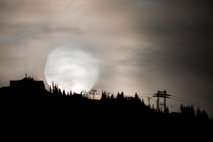 A full moon disappears behind the mountains in Whistler for Halloween.