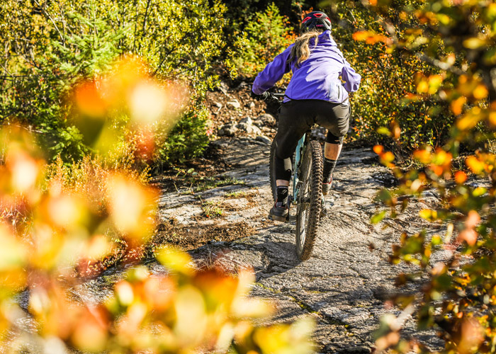 Mountain biker rides over a rock slab on Whistler's Westside trails.