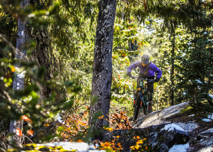 A mountain biker rides through sun and snow on Whistler's Westside trails.