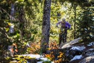 A mountain biker riders through sun and snow on Whistler's West Side trails.