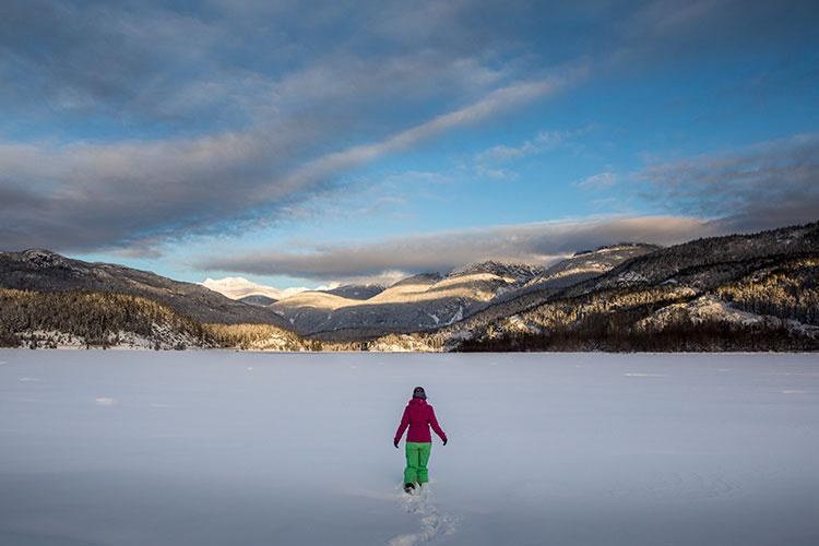 A woman walks across a snow-filled frozen lake.