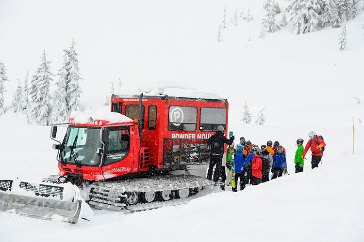 group of people loading into a snowcat on a snowy day