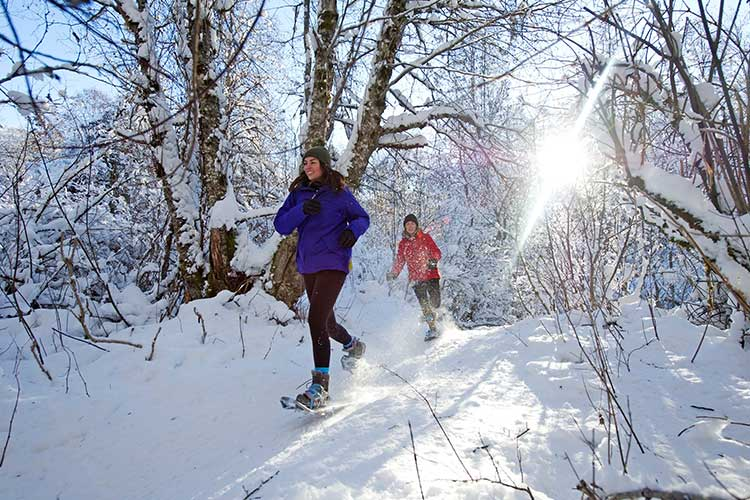 two girls snowshoeing through the forest