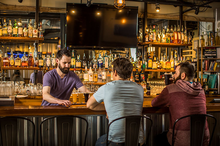 two guys sitting at a bar being served a flight of beer