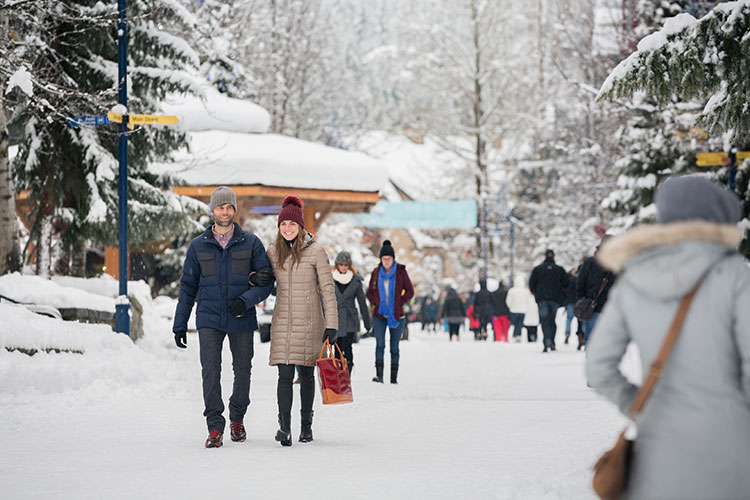 couple walking down a snowy village stroll.