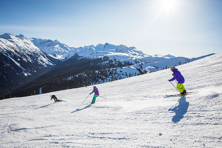 three people skiing on a moderate slope