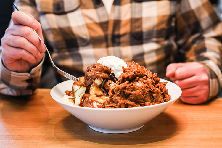 A big bowl of poutine topped with pulled pork and sour cream.