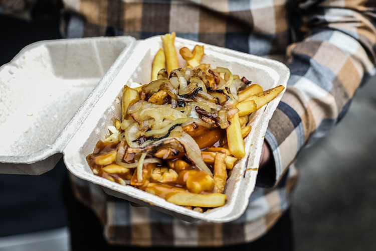 A takeout container piled high with poutine.