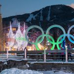 Whistler Village is lit up with festive lights in the trees and glowing Olympic rings.
