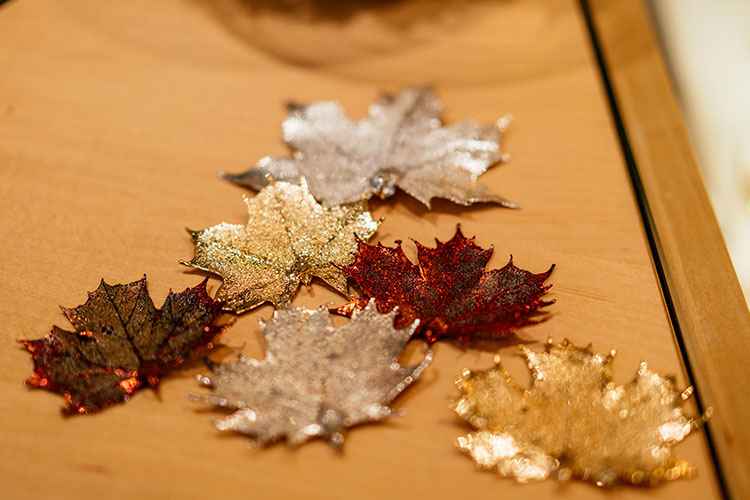 Gold, silver, and brass maple leaf pendants.