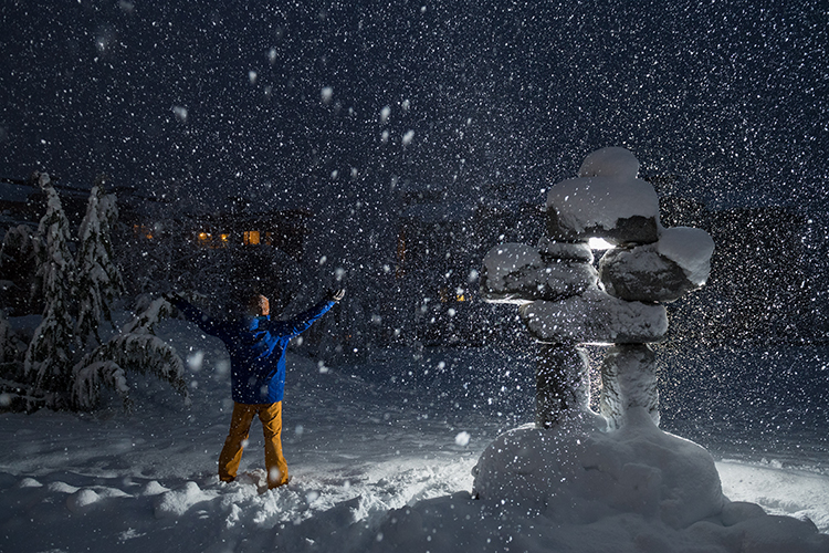 Person holding arms open to snowy sky in Whistler
