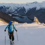 A skier looks over his shoulder at the scenery as he skins up the hill.