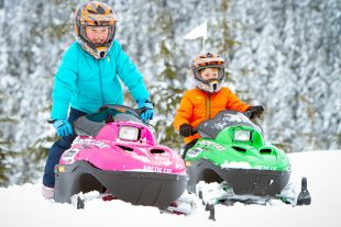 Two kids on mini z snowmobiles.