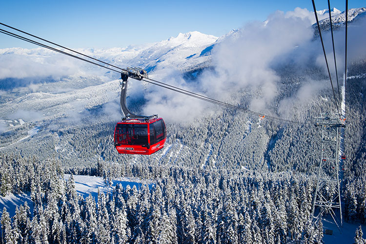 A red Peak 2 Peak Gondola cabin makes its way across the valley from Whistler to Blackcomb Mountain.
