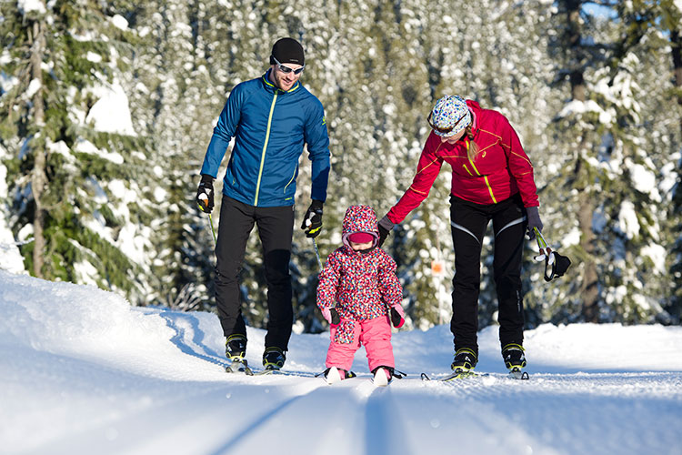 A family enjoy some Nordic skiing with their little one.