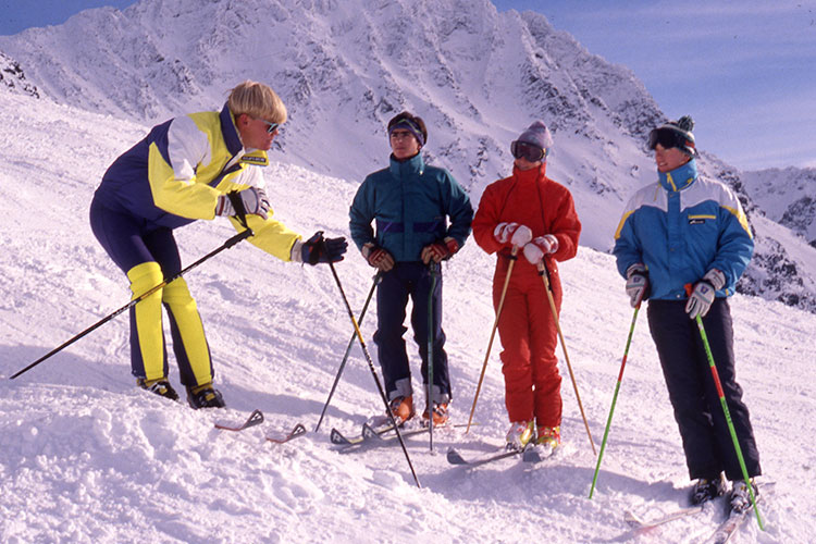 An instructor with a distinctive 80's bowl cut teaches a group of skiers.