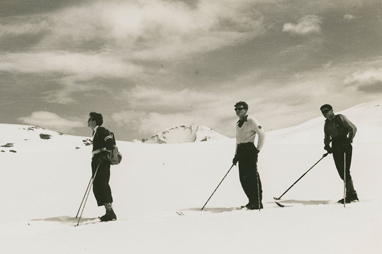 Black and white image of three male skiers in the mountains in sweaters, socks, and sunglasses.