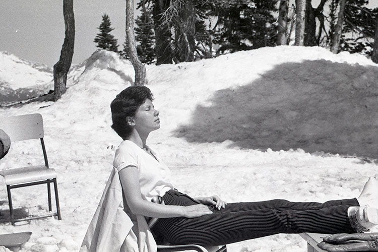 A black and white image of a woman enjoying the sunshine on a chair lift on a spring day in Whistler.