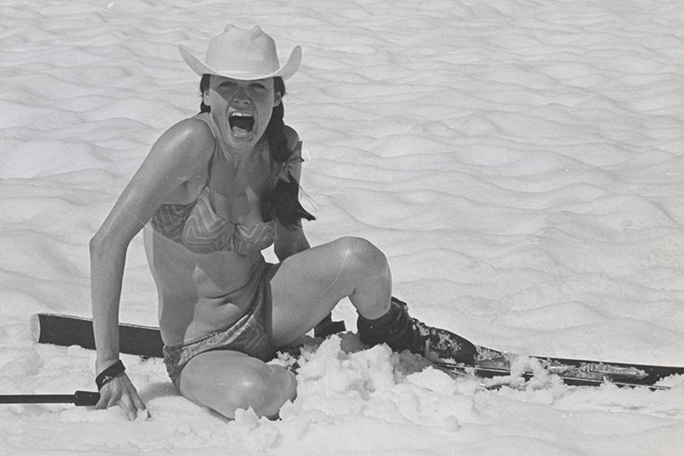 Black and white image of female skier in a bikini on the snow.