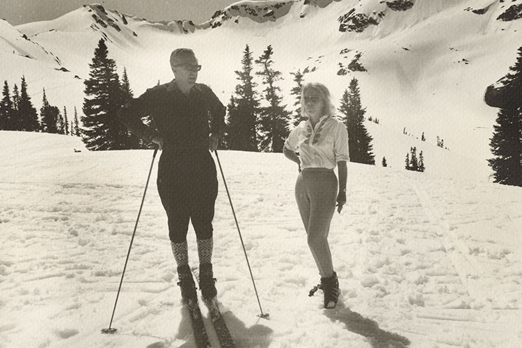 A black and white shot of a man and couple on the ski slopes in Whistler in 1960's attire..