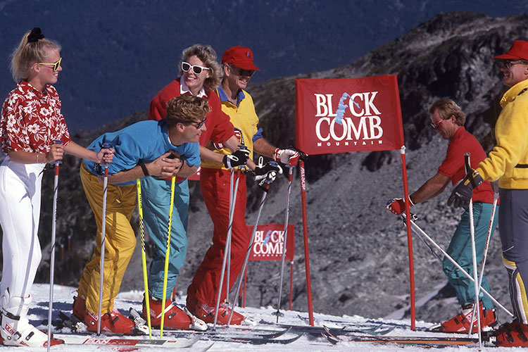 A group of skiers stand in the sun on Blackcomb Mountain.