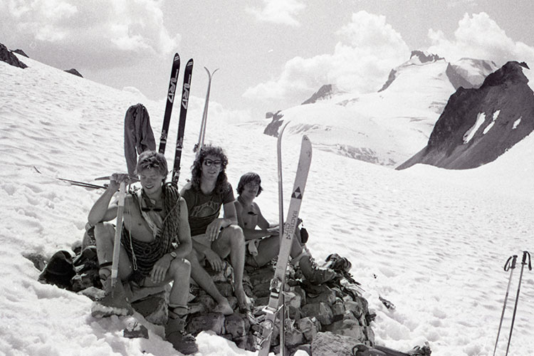 A black and white shot of three male skiers in the backcountry not wearing very much.