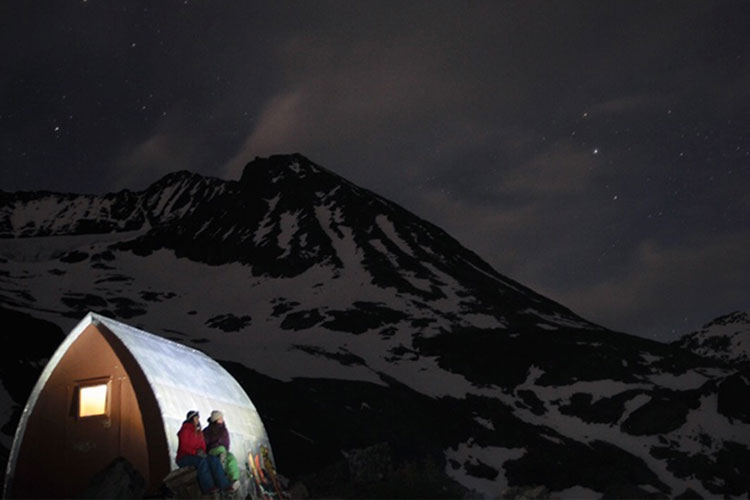 Two backcountry skiers look up at the stars while leaning on the shelter wall at Wedgemount Lake.