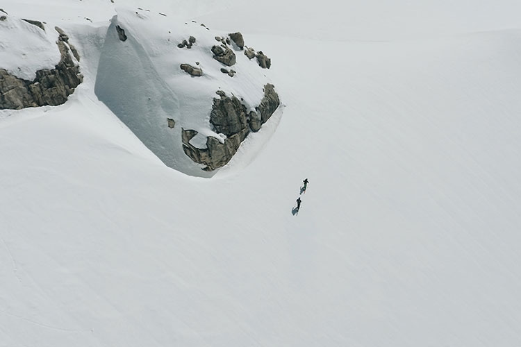 Two backcountry skiers trek through untouched snow to the summit of Rainbow Mountain.