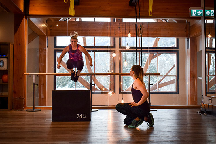 Nina jumps off a box in a gym while her trainer encourages her.