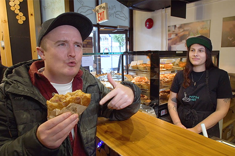 Man eats a meat pie while chatting to an Aussie about why she came to Whistler.