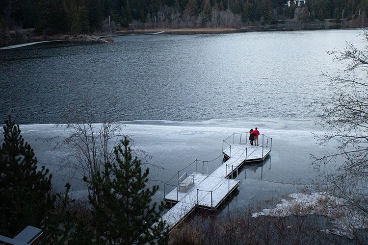 A couple are out on a dock on a lake enjoying the view.