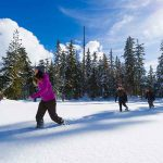 People walking in a snowy field on snowshoes as a budget friendly activity.