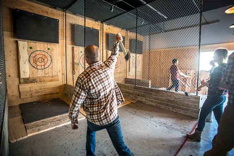 Man throws an axe at a target at this budget friendly activity.