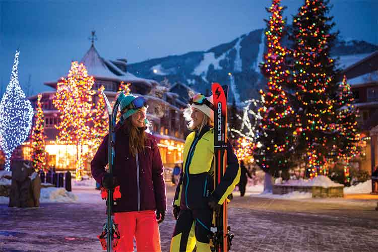 Women skiers on a lit village stroll.