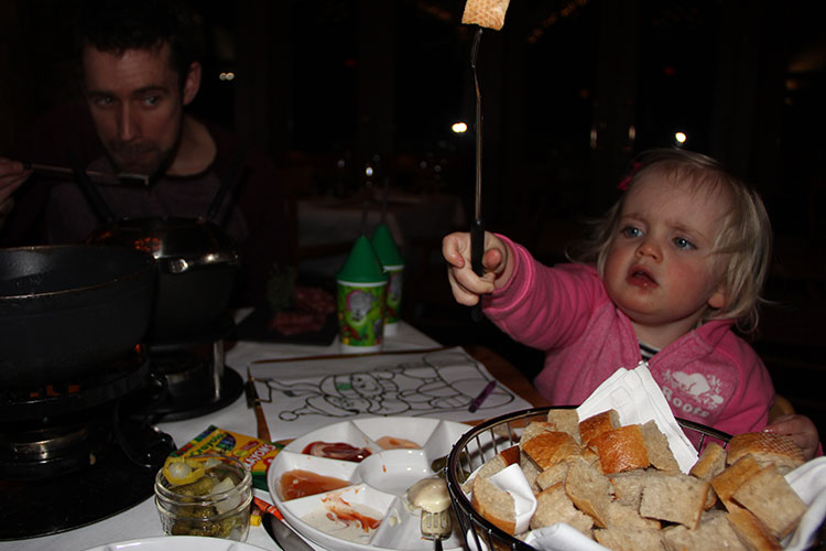 A child waves a long, fondue fork in the air.